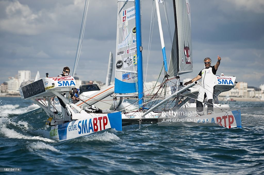 Swiss skipper Yvan Bourgnon (R) gives a thumb as he takes the start with French skipper Vincent Beauvarlet (L) for a one-year trip around the world without assistance on their 6,40m multi hull 'Defi SMA'on October 5, 2013 in Les Sables d'Olonne, western France.