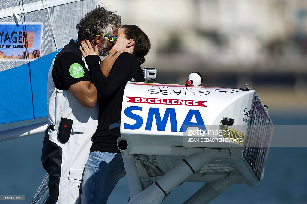Swiss skipper Yvan Bourgnon kisses his wife Nadia before taking the start with French skipper Vincent Beauvarlet for a one-year trip around the world without assistance on their 6,40m multi hull 'Defi SMA'on October 5, 2013 in Les Sables d'Olonne, western France.