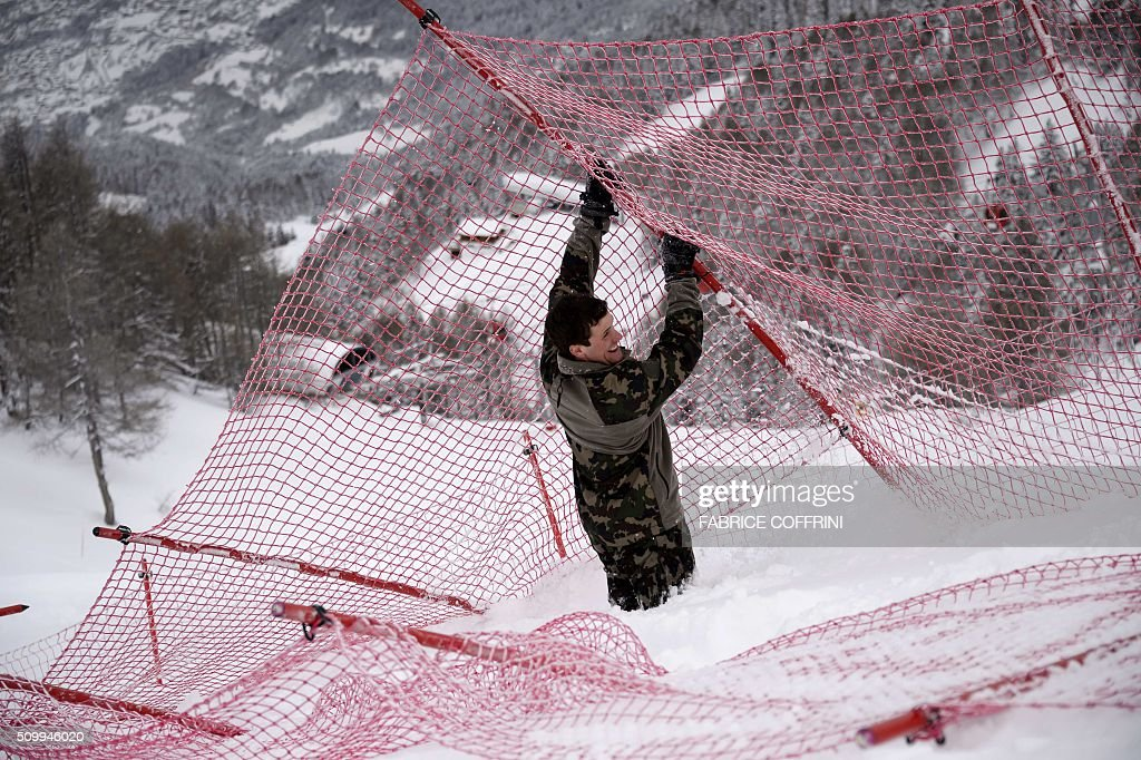 A Swiss soldat remove a net at the FIS Alpine Skiing World Cup in Crans-Montana on February 13, 2016. The women's downhill race has been delayed to February 14, 2016 due to the major snowfall. / AFP / FABRICE COFFRINI