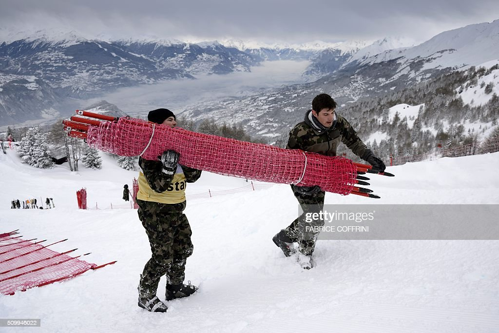 Swiss soldats remove a net at the FIS Alpine Skiing World Cup in Crans-Montana on February 13, 2016. The women's downhill race has been delayed to February 14, 2016 due to the major snowfall. / AFP / FABRICE COFFRINI
