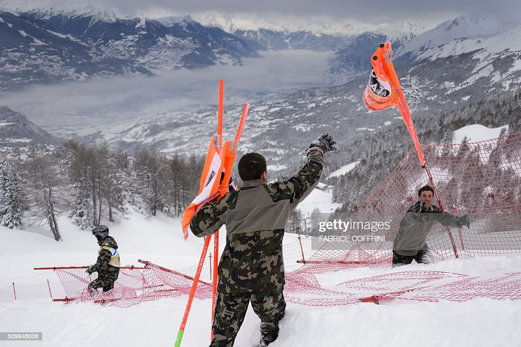 Swiss soldats remove gates at the FIS Alpine Skiing World Cup in Crans-Montana on February 13, 2016. The women's downhill race has been delayed to February 14, 2016 due to the major snowfall. / AFP / FABRICE COFFRINI
