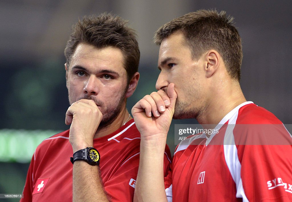 Swiss Stanislas Wawrinka (L) and Marco Chiudinelli speak between two points against Czech Tomas Berdych and Lukas Rosol during a Davis Cup World Group first round tennis match between Switzerland and title owner the Czech Republic on February 2, 2013 in Geneva. AFP PHOTO / SEBASTIEN FEVAL