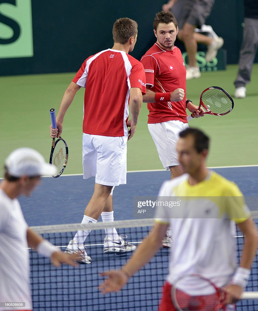 Swiss Stanislas Wawrinka (R) and Marco Chiudinelli speak between two points against Czech Tomas Berdych and Lukas Rosol during a Davis Cup World Group first round tennis match between Switzerland and title owner the Czech Republic on February 2, 2013 in Geneva.