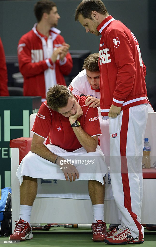Swiss Stanislas Wawrinka is comforted by his captain Severin Luethi after losing his Davis Cup World Group first round tennis match against The Czech Republic on February 3, 2013 in Geneva.