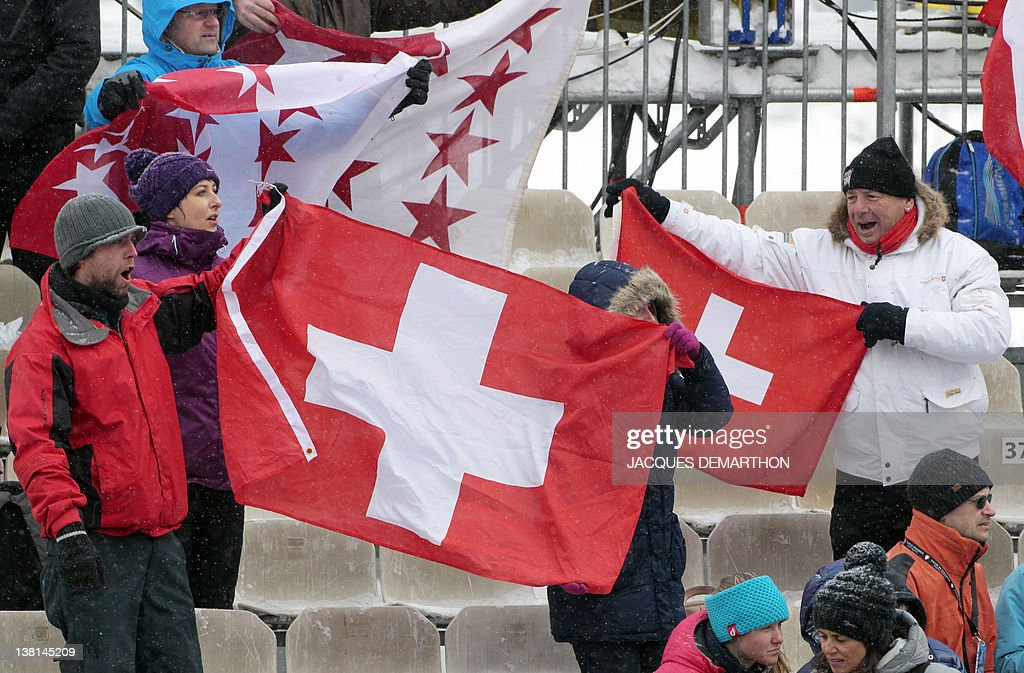 Swiss supporters wave the Swiss national flag at the end of the World Cup downhill of Chamonix on February 3, 2012 in Les Houches near Chamonix, French Alps. Swiss Didier Cuche placed third of the event. DEMARTHON