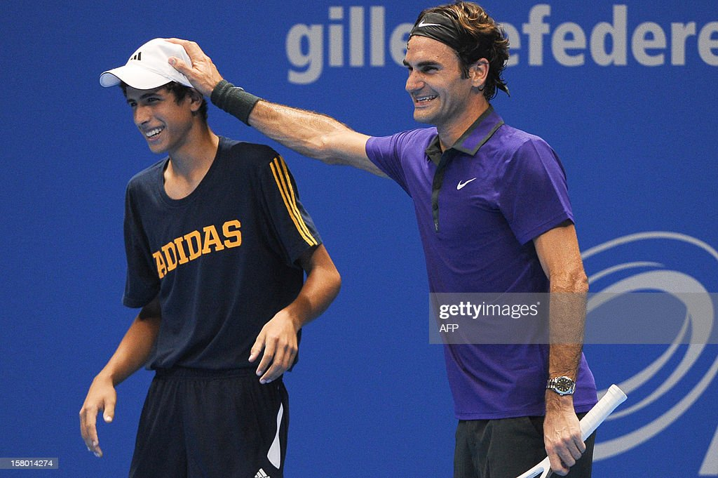 Swiss tennis player Roger Federer asks to a ballboy to play for him against French Jo-Wilfried Tsonga during an exhibition match held at the Ibirapuera Gymnasium in Sao Paulo, Brazil, on December 8, 2012. AFP PHOTO/Yasuyoshi CHIBA