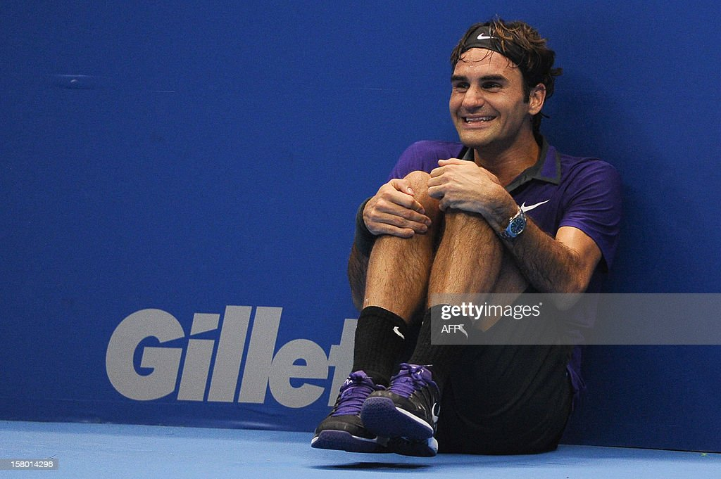 Swiss tennis player Roger Federer jokes to watch the game as as he asks a ballboy to play with French Jo-Wilfried Tsonga during an exhibition match held at the Ibirapuera Gymnasium in Sao Paulo, Brazil, on December 8, 2012. AFP PHOTO/Yasuyoshi CHIBA