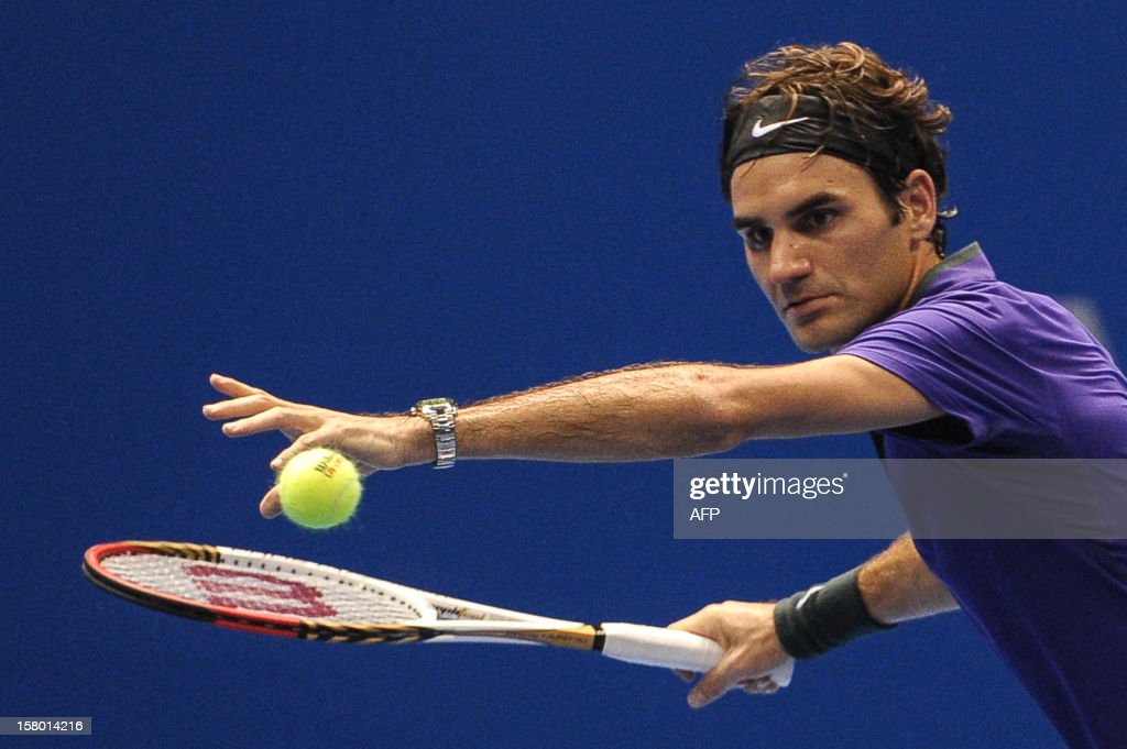 Swiss tennis player Roger Federer returns a shot against French Jo-Wilfried Tsonga during an exhibition match held at the Ibirapuera Gymnasium in Sao Paulo, Brazil, on December 8, 2012. AFP PHOTO/Yasuyoshi CHIBA