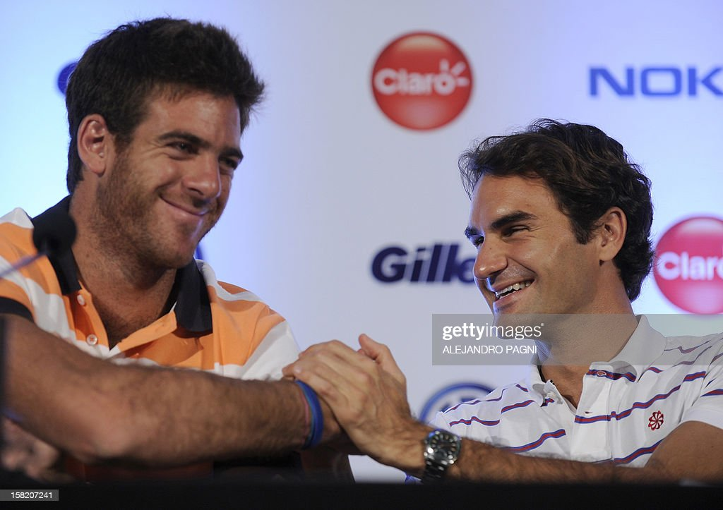 Swiss tennis player Roger Federer(R) shakes hands with Argentinian Juan Martin Del Potro during a press conference in Tigre, near Buenos Aires on December 11, 2012, ahead two exhibition matches that will be held on December 12 and 13. AFP PHOTO / Alejandro PAGNI