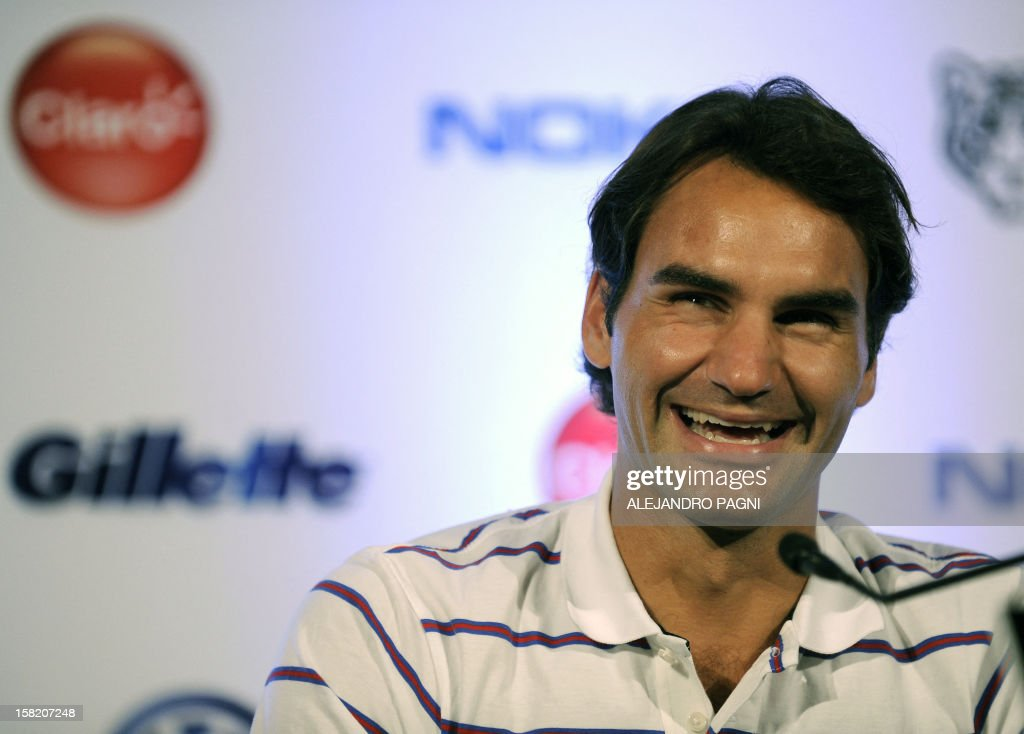 Swiss tennis player Roger Federer(R) smiles during a press conference with Argentinian Juan Martin Del Potro (not in picture), in Tigre, near Buenos Aires, on December 11, 2012, ahead two exhibition matchs that will be held on 12 and 13 December. AFP PHOTO / Alejandro PAGNI