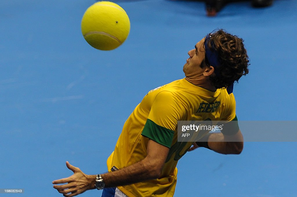 Swiss tennis player Roger Federer, wearing a Brazilian national football team uniform, controls a giant tennis ball during an exhibition match against German Tommy Haas, at the Ibirapuera Gymnasium in Sao Paulo, Brazil, on December 9, 2012. AFP PHOTO/Yasuyoshi CHIBA