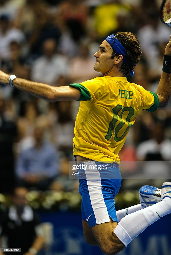 Swiss tennis player Roger Federer, wearing a Brazilian national football team uniform, jumps to smash the ball during an exhibition match against German Tommy Haas, at the Ibirapuera Gymnasium in Sao Paulo, Brazil, on December 9, 2012. AFP PHOTO/Yasuyoshi CHIBA