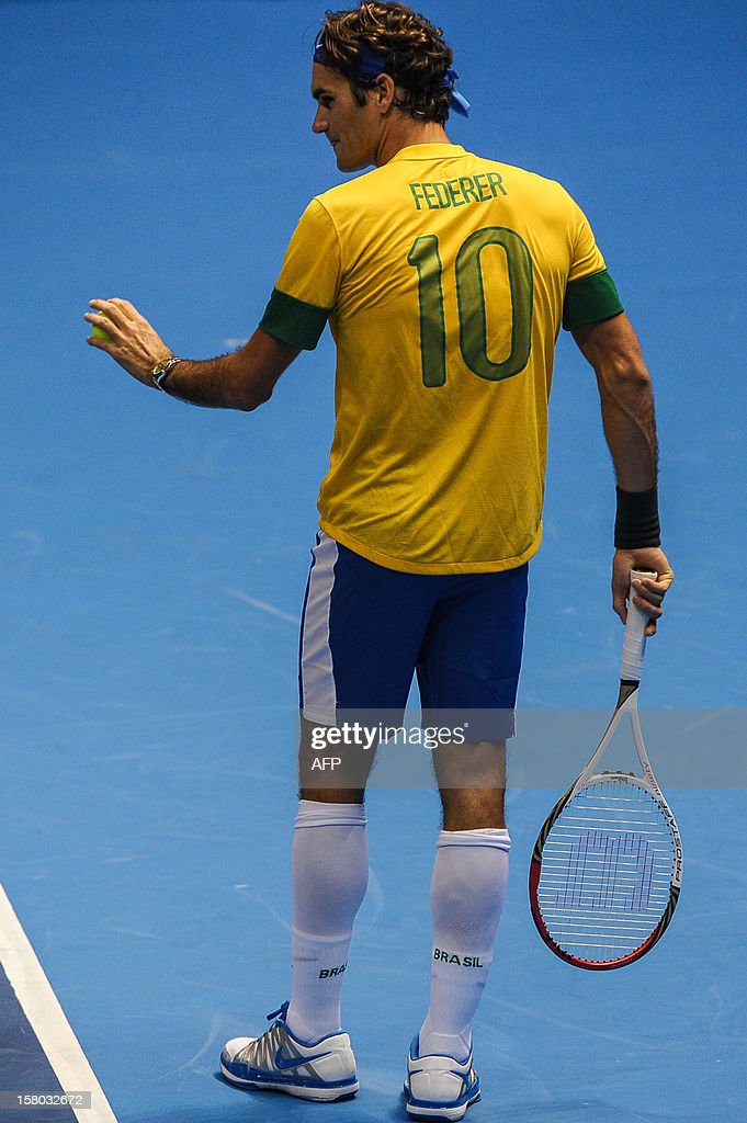 Swiss tennis player Roger Federer, wearing a Brazilian national football team uniform, prepares to serve a ball during an exhibition match against German Tommy Haas, at the Ibirapuera Gymnasium in Sao Paulo, Brazil, on December 9, 2012. AFP PHOTO/Yasuyoshi CHIBA
