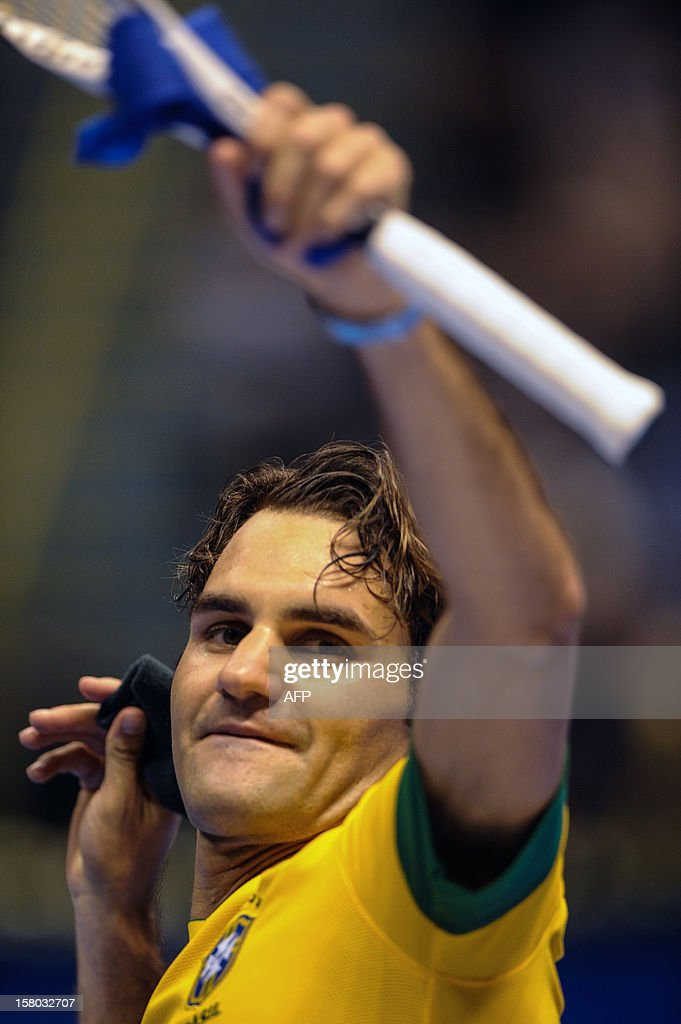 Swiss tennis player Roger Federer, wearing a Brazilian national football team uniform, throws his wrist band to fans after his final exhibition match against German Tommy Haas, at the Ibirapuera Gymnasium in Sao Paulo, Brazil, on December 9, 2012. AFP PHOTO/Yasuyoshi CHIBA