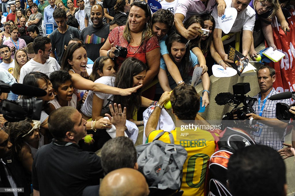 Swiss tennis player Roger Federer, wearing a Brazilian national football team uniform, signs autographs to fans after an exhibition match against German Tommy Haas, at the Ibirapuera Gymnasium in Sao Paulo, Brazil, on December 9, 2012. AFP PHOTO/Yasuyoshi CHIBA