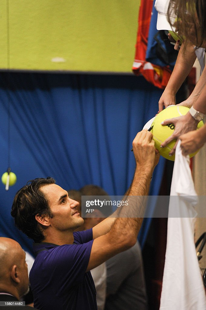 Swiss tennis player Roger Federer writes his autographs to fans after an exhibition match against French Jo-Wilfried Tsonga held at the Ibirapuera Gymnasium in Sao Paulo, Brazil, on December 8, 2012. AFP PHOTO/Yasuyoshi CHIBA