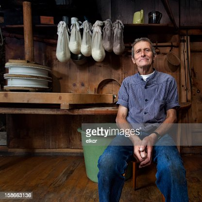 Swiss Traditional Cheesemaker Smiling In Wooden Farmhaus.