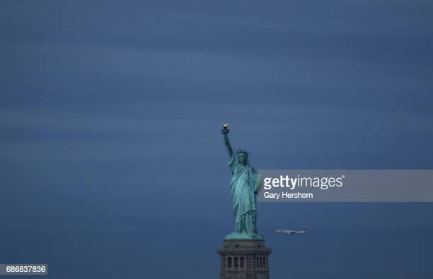 Swissair airplane flies past the Statue of Liberty on May 21 2017 in New York City