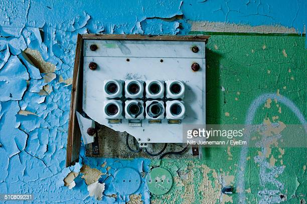 Switchboard and peeling paint on abandoned building wall