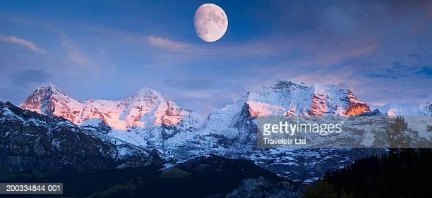 Switzerland, Berner Oberland, moon over mountains, dusk