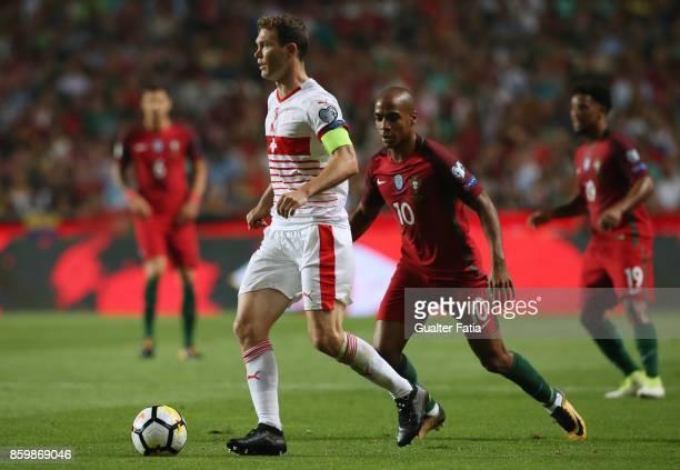 Switzerland defender Stephan Lichtsteiner with Portugal midfielder Joao Mario in action during the FIFA 2018 World Cup Qualifier match between...