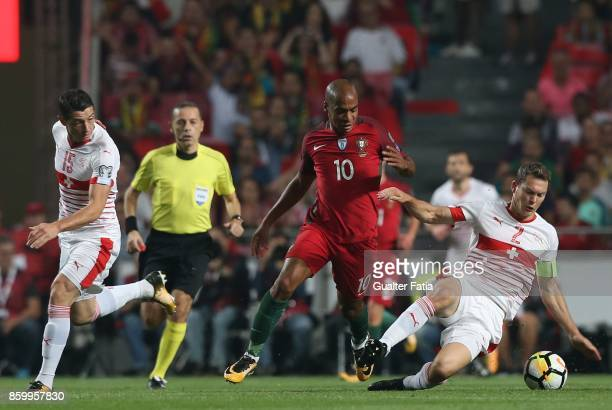 Switzerland defender Stephan Lichtsteiner with Portugal midfielder Joao Mario and Switzerland midfielder Blerim Dzemaili in action during the FIFA...