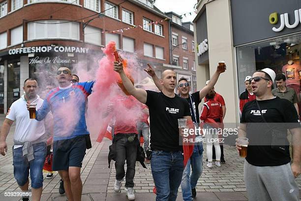 Switzerland fans carrying a flare arrive at a fan ahead of the Euro 2016 group A football match between Albania and Switzerland in Lens on June 11...
