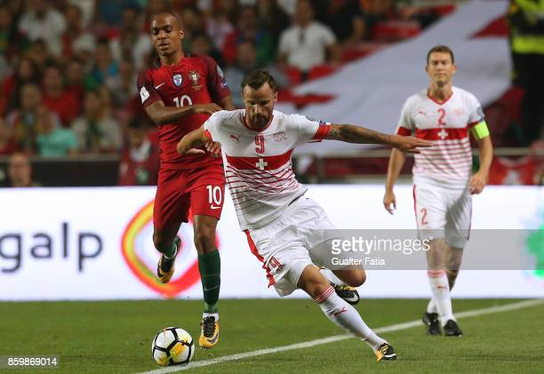 Switzerland forward Haris Seferovic with Portugal midfielder Joao Mario in action during the FIFA 2018 World Cup Qualifier match between Portugal and...