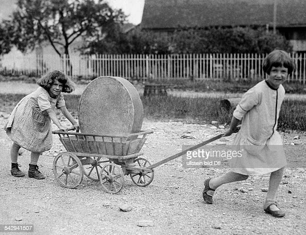 Switzerland FreiburgKanton Fribourg Freiburg Rural population Two girls transport a Gruyère cheese on a handcart 1931 Published by 'Berliner...