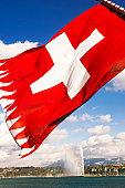 Switzerland, Geneva, Lake Geneva, Swiss flag in foreground