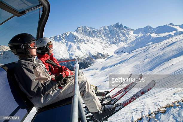 Switzerland, Graubuenden, Savognin, Children's (8-9) in ski lift, side view