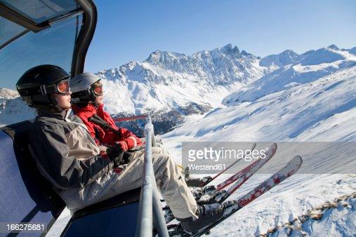 Switzerland, Graubuenden, Savognin, Children's (8-9) in ski lift, side view