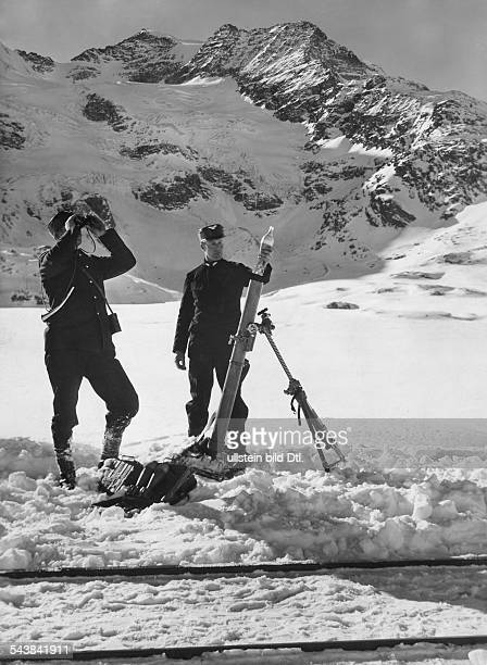 Upper Engadin Bernina Express in wintertime linesmen at the tracks with a mortar which is used to set off avalanches 1954 Photographer Steiner...