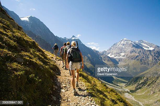 Switzerland, Kandersteg, four hikers on footpath, rear view