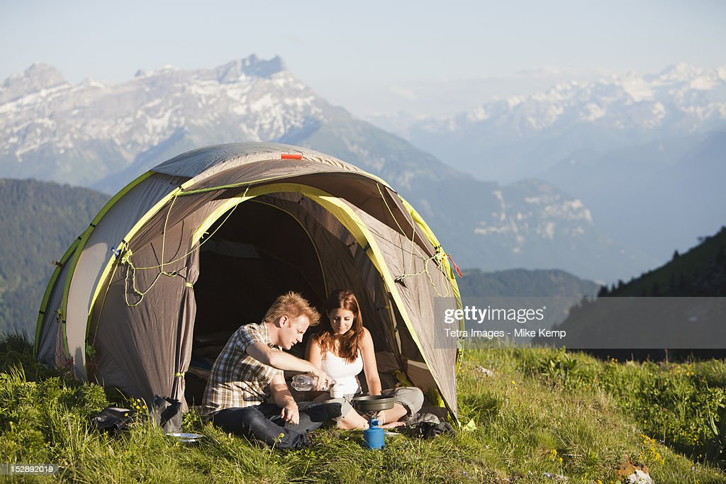 Switzerland, Leysin, Hikers preparing breakfast on Alpine meadow