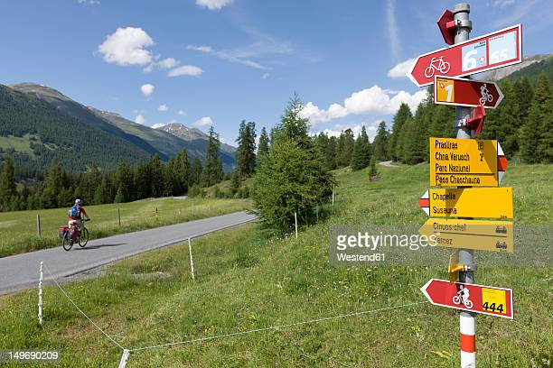 Switzerland, Mature man cycling on country road, directional sign in foreground