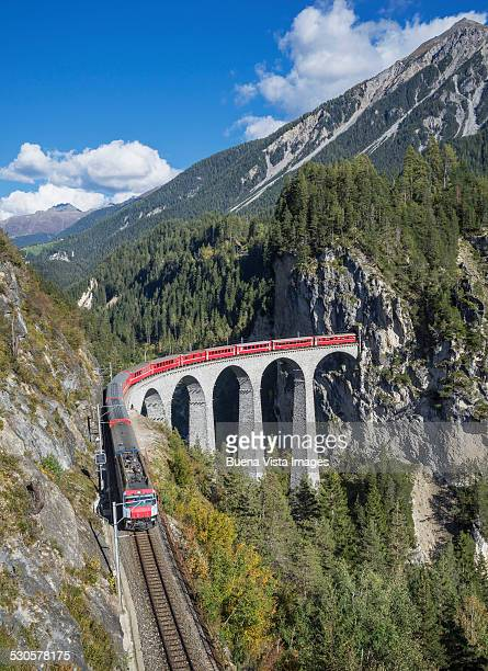 Switzerland, red train on a Viaduct