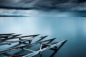 Switzerland, Vaud, Villette, Lake Leman, Slipway in still lake with storm clouds on horizon