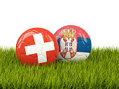 Switzerland vs Serbia. Soccer concept. Footballs with flags on green grass. 3D illustration