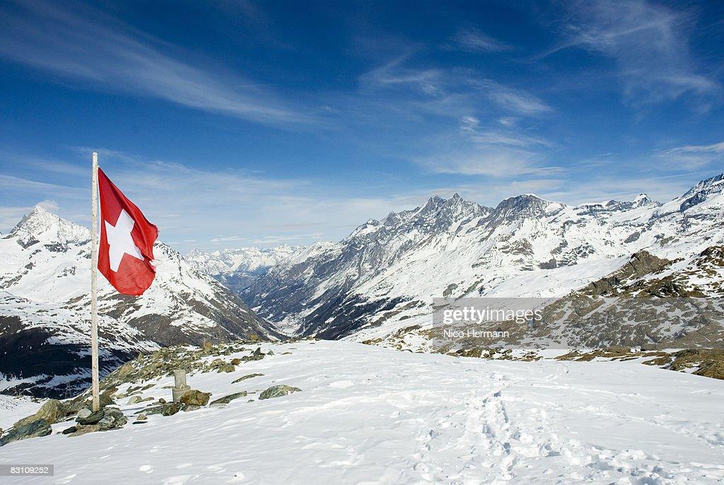 Switzerland, Wallis, The Alps, Swiss flag on snowcapped mountain