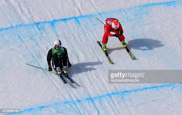 Switzerland's Armin Niederer and Finland's Jouni Pellinen compete in the Men's Freestyle Skiing Ski Cross 1/8 Finals at the Rosa Khutor Extreme Park...