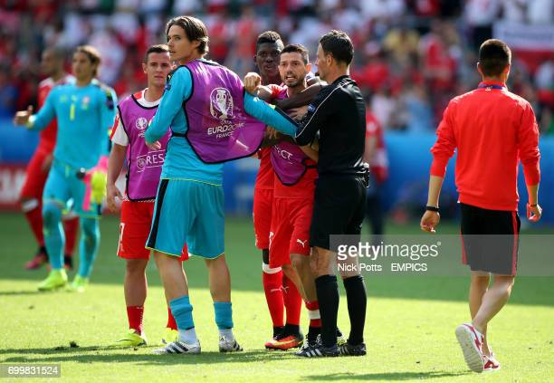 Switzerland's Blerim Dzemaili is held back by teammate Marwin Hitz and match referee Mark Clattenburg