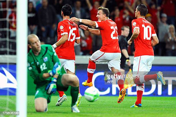 Switzerland's Blerin Dzemali and Xhredan Shaqiri and Granit Xhaka celebrate after scoring a goal by penalty against Iceland during a FIFA World Cup...