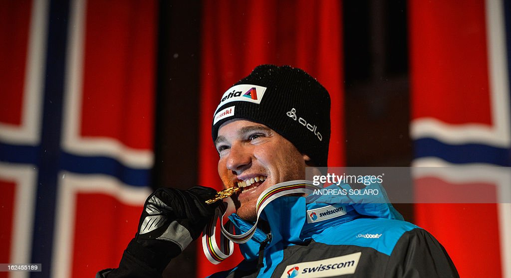 Switzerland's Dario Cologna poses on February 23, 2013 with his gold medal on the podium of the men's cross country 15 kms classic +15 km free Skiathlon race of the FIS Nordic World Ski Championships at the Val Di Fiemme Cross Country stadium in Cavalese, northern Italy.