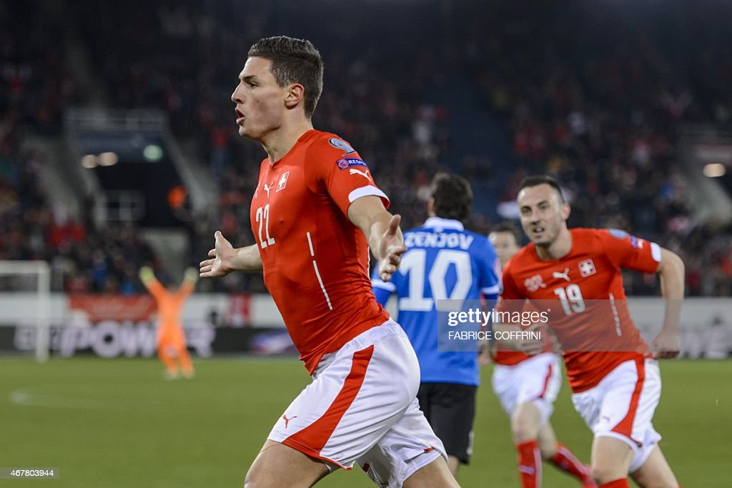 Switzerland's defender Fabian Schaer (L) celebrates with teammate forward Josip Drmic after he scored the first goal during the Euro 2016 qualifying football match between Switzerland and Estonia at the Swissporarena stadium in Lucerne on March 27, 2015. AFP PHOTO / FABRICE COFFRINI
