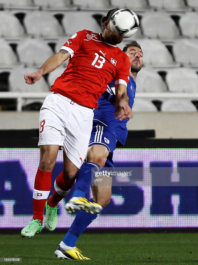 Switzerland's defender Ricardo Rodriguez (R) heads the ball next to Cyprus' midfielder Anthos Solomou during the 2014 World Cup European zone group E qualifying football match between Cyprus and Switzerland at GSP Stadium in Nicosia on March 23, 2013.
