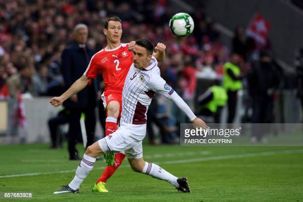 Switzerland's defender Stephan Lichtsteiner vies with Latvian forward Davis Ikaunieks during the WC 2018 qualifying football match Switzerland vs...