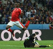 TOPSHOT Switzerland's forward Breel Embolo jumps over France's goalkeeper Hugo Lloris during the Euro 2016 group A football match between Switzerland...