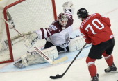 Switzerland's forward Denis Hollenstein attacks the net of Latvia's goalie Kristers Gudlevskis during a preliminary round group B game Latvia vs...
