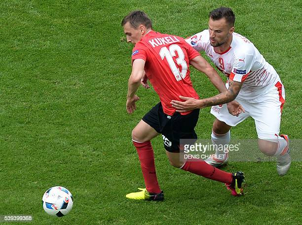Switzerland's forward Haris Seferovic challenges Albania's midfielder Burim Kukeli during the Euro 2016 group A football match between Albania and...